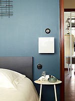 In the bedroom, the walls are painted in Farrow & Ball's Hague Blue, The light switches are Hager's 1930 series and a vintage 1970s era wall light hangs above the simple bedside table.