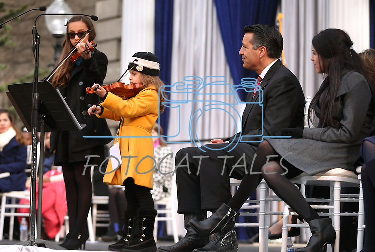 "Gov. Brian Sandoval and his daughter Maddy, right, listen to a performance of ""Home Means Nevada"" by Alexia Ciobanu, 7, and Haylee Reynolds, 13, during the inauguration on the steps of the Capitol, in Carson City, Nev., on Monday, Jan. 5, 2015. (Las Vegas Review-Journal/Cathleen Allison)"