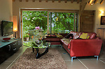 The interior of Chobbs Barn Self catering accommodation in Eye, Suffolk, England showing the open plan living space with red leather sofa with Isamu Noguchi coffee table and sliding patio doors into garden area under the old walnut tree