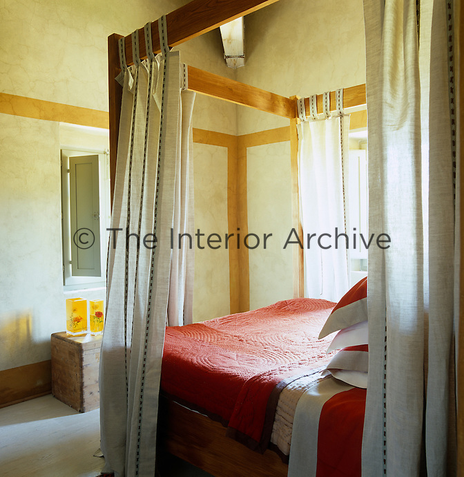 Linen curtains are draped around this wooden four-poster bed which is covered in a red quilt