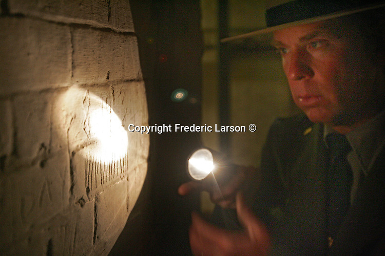 A behind scene tour with Park Ranger John Cantwell on Alcatraz as he shines a flash light on markings made on prison wall in the dungeon of Alcatraz Island in the San Francisco Bay.