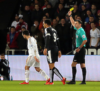 Match referee Michael Oliver (R) shows Leon Britton of Swansea (L) a yellow card during the Barclays Premier League match between Swansea City and Watford at the Liberty Stadium, Swansea on January 18 2016