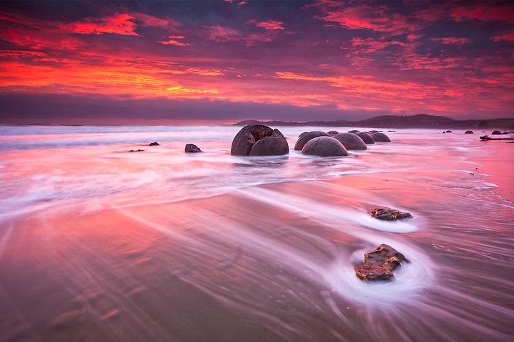 Moeraki Boulders and a vivid red dawn, Coastal Otago, South Island, New Zealand - stock photo, canvas, fine art print