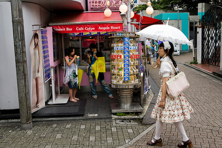 A fashionably dressed young woman walks past the Angels heart dessert bar in Shibuya District, Tokyo, Japan.