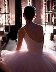Young female dancer in a pink tutu sitting down watching from the wings