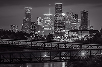 We captured Rosemont pedestrian bridge and the Houston skyline over the Buffalo Bayou at night in downtown area of the city in black and white.  Houston has a lot to offer with many parks, cultural events in the theater district, along with many sport and music event to name yet a few things to do.  Houston also has a reputation of a place to see top notched performing art along with access to several museums in the area. The Theater distric performing art has nine major performing art group along with six performance halls. You can see Opera, a plays, the ballet and any number of music events including the well known Houston Symphony Orchestra Houston has some top notch restaurants and places to stay.  Houston has a population of around 3.4 million people it the largest city in Texas and the fourth largest in the nation. The skyline of Houston is a very impressive site with some of the tallest modern skyscrapers buildings in the US. In this image you can see the Heritage Plaza, Chevron, Wells Fargo and the tallest building in Houston the J P Morgan Chase Tower at 1002 ft and it is the 17 tallest in the US. Houston is the seat of Harris county and was founded in 1837 near the banks of the Buffalo Bayou or Allen Landing as it is called today.