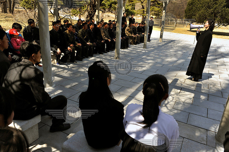 A woman addresses a group of students visiting the birthplace of Kim Il-sung.