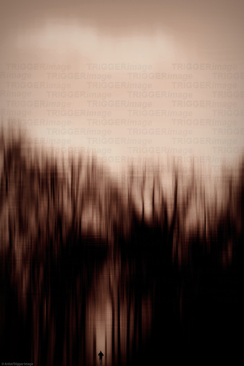 The abstract blur of in row standing trees with the silhouette of a pedestrian.