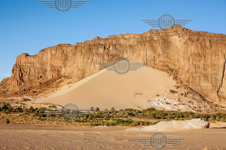 A sand dune that has form against a cliff, both created by wind erosion, on the Ennedi Plateau.