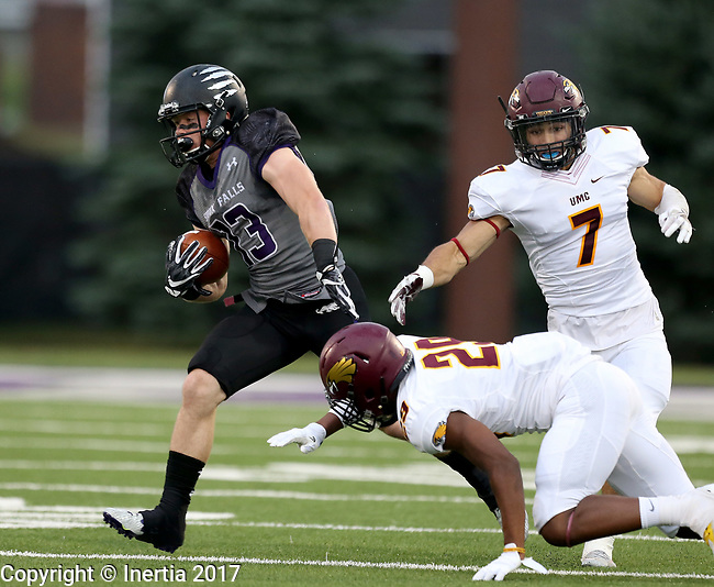 SIOUX FALLS, SD - SEPTEMBER 23: Winston Maxwell #23 from the University of Sioux Falls looks to shake the tackle of Anfernee Cooper #29 from Minnesota Crookston in the first half of their game Saturday night at Bob Young Field in Sioux Falls. (Photo by Dave Eggen/Inertia)