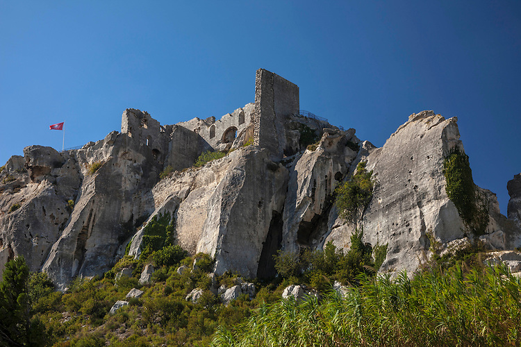 The deserted citadel of Les Baux is incorporated into the natural rocky plateau overlooking the agricultural farmland below.