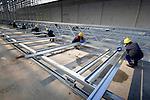 UTRECHT - Op het Utrechtse bedrijventerrein wordt met opmerkelijk veel menskracht, met hulp van een grote groep van ongeveer 20 Polen, gewerkt aan de opbouw van het aluminium frame van een nieuw distributiecentrum voor de Hema. Het door bouwbedrijf Van de Ven uit Veghel te bouwen complex wordt ruim dertig meter hoog en meer dan honderd meter lang en gaat ruimte bieden voor 300 miljoen produkten. In de het gebouw dat 25 miljoen euro gaat kosten, worden van 2008 de zgn push-artikelen (vooral actie- en seizoensartikelen) geheel geautomatiseerd opgeslagen en verdeeld. Omdat de Polen ieder voor zich als kleine zelfstandige werken en zelf zorg moeten dragen voor verzekeringen en premies, zijn ze goedkope werknemers. COPYRIGHT TON BORSBOOM ANP PHOTO COPYRIGHT TON BORSBOOM