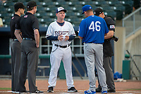 Northwest Arkansas Naturals manager Darryl Kennedy (8) (center) talks with Tulsa Drillers manager Scott Hennessey (46) and the umpires on May 13, 2019, at Arvest Ballpark in Springdale, Arkansas. (Jason Ivester/Four Seam Images)