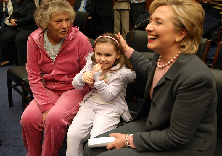Hillary Rodham Clinton, D-N.Y., talks with Tylerann Zadroga daughter of deceased 9/11 responder James Zadroga during a news conference with sick 9/11 first responders to call for 9/11 health funding in the FY2008 budget. Tylerann's grand mother Linda Zadroga is in background..