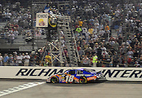 May 1, 2009; Richmond, VA, USA; NASCAR Nationwide Series driver Kyle Busch takes the checkered flag to win the Lipton Tea 250 at the Richmond International Raceway. Mandatory Credit: Mark J. Rebilas-