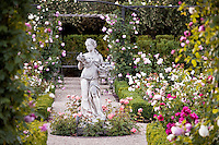 Statue of classical woman as focal point in axis of rose garden.