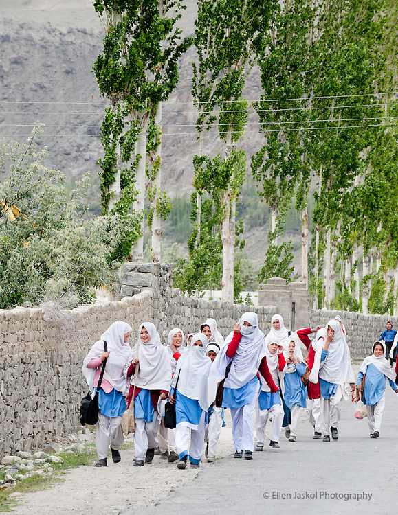 May 26, 2011. School children walk home after classes in Bagardu, where many attend Central Asia Institute's Bagardu Anwar Shaheed Public School, outside of Skardu.   The girl walking alone attends the CAI school.  Photographed on our six-hour drive from Gilgit to Skardu.  Girls tend to their goats on the dried river bed of the Indus River.  Photo by Ellen Jaskol.