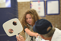 NWA Democrat-Gazette/FLIP PUTTHOFF <br />HAIR RAISING EXPERIMENT<br />Sophia Marcum, a kindergarten student at Eastside Elementary in Rogers, watches her hair stand on end Tuesday June 5 2018 during a science experiment with Steve Cox, presenter of Super Science education and entertainment programs. Cox did several experiments for students including making snow with soap and carbon dioxide, forming tornadoes in soda bottles, and using a chemical reaction to create a giant ice cream cone. The experiments taught students about the types of matter, evaporation and different types of gasses.
