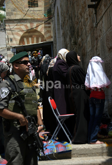 Israeli soldiers stand guard as Palestinian women perform the first Friday prayer of the holy Muslim month of Ramadan in front of the closed Ibrahimi mosque in the West Bank city of Hebron on Aug. 5, 2011. Photo by Najeh Hashlamoun