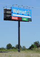 NWA Democrat-Gazette/ANDY SHUPE<br /> Traffic passes Thursday, Aug. 20, 2015, a sign for the Walmart Supercenter on Elm Springs Road in Springdale. Springdale has the largest maximum allowance for height and square footage of sign faces out of Springdale, Fayetteville, Rogers and Bentonville. The current maximum allowances in Springdale are 60 feet for height and 400 square feet for sign faces. Officials are looking to reduce this to maximum allowances of 30 feet for height and 150 square feet for sign faces.