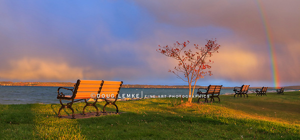 Benches and colorful storm clouds with a rainbow over Traverse Bay in early morning at Elk Rapids, Michigan, USA