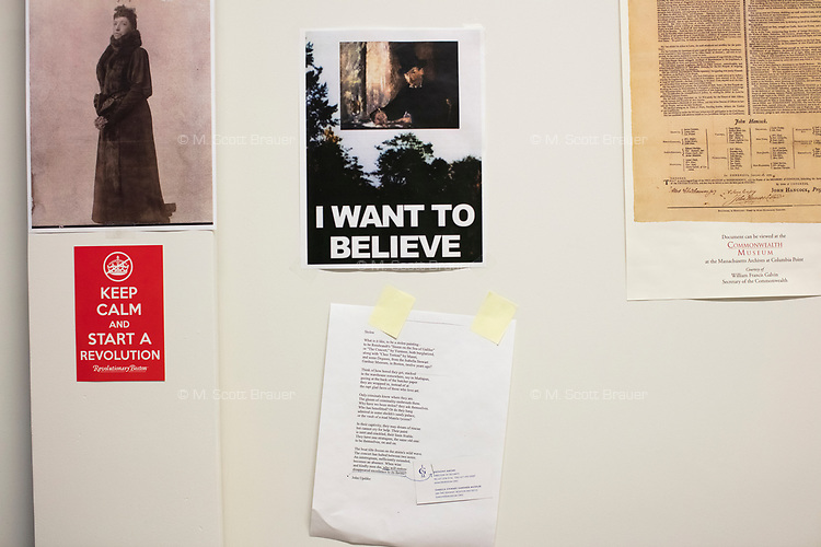 """A poster and a poem hang on a wall in the office of Anthony Amore, the Directory of Security and Chief Investigator at the Isabella Stewart Gardner Museum in Boston, Mass., USA, seen here on Tues., Dec. 5, 2017. The poster on top, reminiscent of Fox Mulder's """"I Want to Believe"""" poster in the X-Files, features a reproduction of Manet's """"Chez Tortoni"""" in place of the UFO. The poem is a piece written by John Updike about the Gardner Museum theft.  Part of Amore's ongoing work is the investigation into the 1990 theft of 13 pieces from the museum: 10 paintings, 2 objects, and 1 etching. Among the paintings stolen were works by Rembrandt, Vermeer, Degas, and Manet. """"Chez Tortoni"""" is one of the paintings that was stolen in the heist. At left, is a portrait of Isabella Stewart Gardner."""