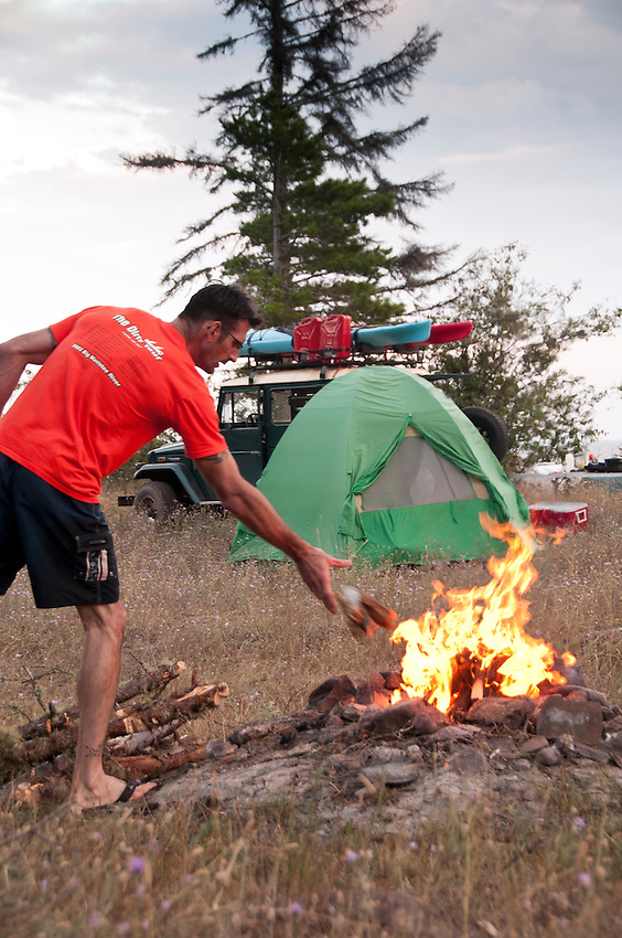 Joe Chmelar of Norton Shores Michigan stokes a campfire at High Rock Bay on the Keweenaw Peninsula during the 2010 U.P. Overland trip in the Upper Peninsula of Michigan.