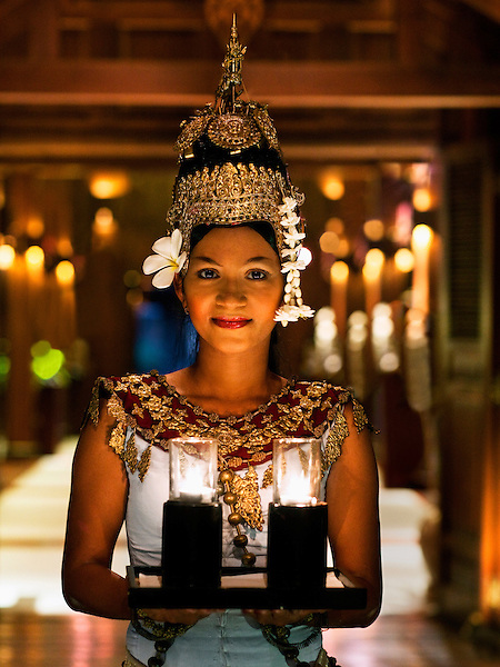 A young Cambodian Apsara dancer welcomes guests with a tray of candles at dusk at the entrance of La Residence d'Angkor, Siem Reap, Cambodia. An Apsara dancer is a classical Khmer dancer.