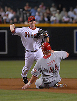 Apr 11, 2007; Phoenix, AZ, USA; Cincinnati Reds center fielder (44) Adam Dunn slides into a double play as Arizona Diamondbacks shortstop (6) Stephen Drew throws to first base in the fourth inning at Chase Field in Phoenix, AZ. Mandatory Credit: Mark J. Rebilas