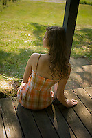 Rear view of young woman sitting on porch leaning on column