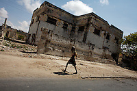 """a man walks down a center street In  Somalia's war torn capital Mogadishu on Tuesday April 22nd 2008.///..Sporadic street fighting between Ethiopian .troops and Islamic fighters trying to bring down Somalia's shaky .government has killed 81 people on April 19 and 20, the head of a .local human rights group said Sunday. .""""The casualties ... were caused by Ethiopians using heavy artillery and .tank shells in residential areas of the war-torn capital. We condemn .this latest fighting,"""" said Sudan Ali Ahmed, chairman of Elman Human .Rights. Besides the 81 dead, 119 people had been wounded, he said. .Reports on Monday April 21 say Ethiopian troops have taken control of a mosque with a large .number of civilians inside following heavy fighting with insurgents. .The reports say a number of civilians were killed inside the mosque and others are being held by Ethiopians against .their will. .This apparent increase in the brutality of attacks may be caused partly by a .recent American decision to classify the Shabab (youth), the Islamic Courts .Union's former military wing, as a terrorist group. Battered by Ethiopian attacks .and by infighting between sub-clans engaged in the insurgency, Shabab .fighters now probably number fewer than 400. But America's decision to .demonise them has boosted jihadist commanders such as Aden Hashi Ayro, .strengthening his reputation for piety and anti-Americanism, which has itself .been boosted by recent missile attacks that have accidentally killed civilians...Philippe Lazzarini, head of the UN Office for the Coordination of Humanitarian Affai .rs (OCHA) Somalia, said on Monday April 21st that the combination of a severe drought, civil insecurity and h .yperinflation was pushing the country to the brink. If the situation were happening a .nywhere else """"it would have triggered outrage"""". .Lazzarini said Somalia was """"on the eve of a massive, massive humanitarian catast .rophe"""", with an estimated 2.5 million people needing assistance. .""""If things"""