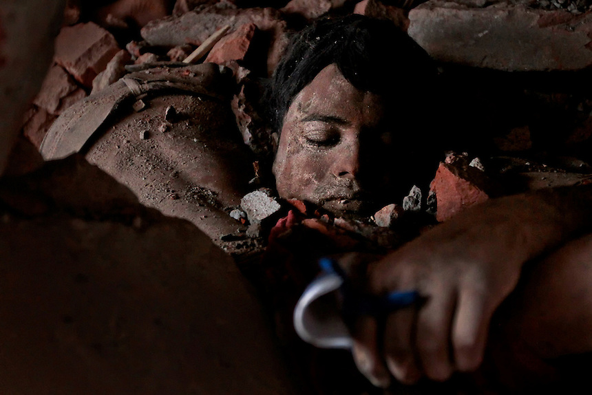 A victim's body lies amid rubble at the site of a collapsed garment factory in Savar, Bangladesh,Thursday, April 25, 2013.