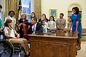 Washington, DC - October 29, 2009 -- United States President Barack Obama talks with MacKenzie Clare, 14, and the other Girls Scouts after signing the Girl Scouts USA Centennial Commemorative Coin Act in the Oval Office, October 29, 2009. First Lady Michelle Obama looks on at right. .Mandatory Credit: Pete Souza - White House via CNP