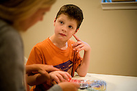 "Jack Ursitti, age 7, works on a learning activity with his teacher Sarah Hoey, of the Nashoba Learning Group, in his home in Dover, Mass., on Monday, July 25, 2011.  Hoey has been working with Jack since he was 3. ""He was completely non-verbal when I met him,"" she said. Now Jack can spell basic words and speak at a basic level...Jack has been diagnosed with autism.  After school at his home, Jack works with his teacher and a therapist to do educational and independent leisure activities. ..Hoey spends 1 or 2 days a week after school with Jack...Jack Ursitti wears a small GPS ankle bracelet at all times in case he runs off from his family or caretakers. The device will be activated if he goes missing, allowing police and other searchers to find him."