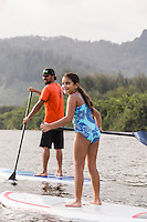 A girl looks back while learning how to standup paddle with her family on the Wailua River, Kaua'i.