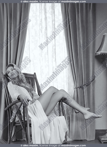 Romantic portrait of a beautiful sensual woman sitting in a rocking chair by the window. Black and white.