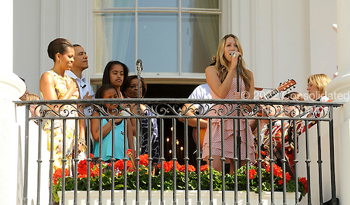 The First Family listens as Colbie Caillat sings the National Anthem before the White House Easter Egg Roll on the South Lawn of the White House in Washington, DC, on Monday, April 25, 2011.  From left are First Lady Michelle Obama, U.S. President Barack Obama, daughters Sasha, and Malia and Michele's mother Marian Robinson.  .Credit: Roger L. Wollenberg / Pool via CNP