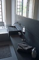 A running tap highlights the dark grey slate wash basin in this minimal bathroom