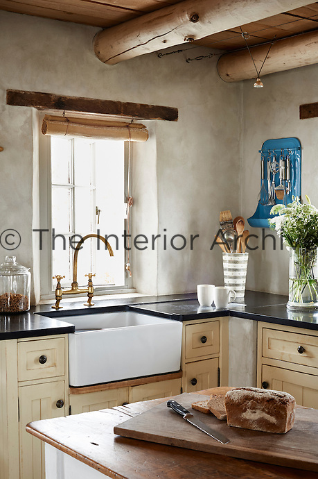 A country kitchen with a beamed ceiling and stone walls. A brass mixer tap sits over a butler sink in front of a plain window with a roller blind.