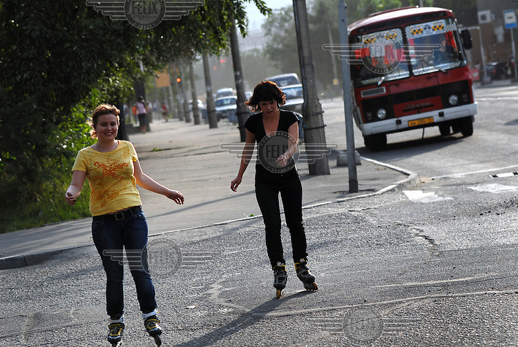Two young women rollerblade down a street in Kyzyl.