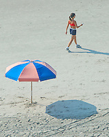 A woman dials a cell phone as she walks along a beach at Virginia Beach, Va.