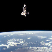 The Earth-orbiting space shuttle Challenger beyond the Earth's horizon was captured by a 70mm camera onboard the unmanned, free-flying Shuttle Pallet Satellite (SPAS-01) during the busy flight day 5 of the STS-7 mission in June 22, 1983. Visible in the cargo bay are the protective cradles for the now-vacated Telesat Anik C-2 and Palapa B communications satellites, the pallet for the NASA Office of Space and Terrestrial Applications (OSTA-02), the Remote Manipulator System (RMS) and the KU-Band antenna. The STS-7 crew with the RMS later retrieved the SPAS and returned it to a stowed position in the cargo bay for return to Earth. .Credit: NASA via CNP