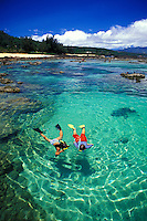 Children (age 8) snorkel in the tidal pools of Shark's Cove (or Pupukea Beach) looking for colorful fishes. Located on Oahu's north shore.