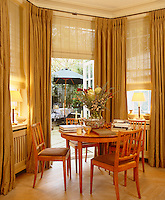 A large bay window hung with gold curtains provides an intimate dining space adjacent to some French windows leading to the garden