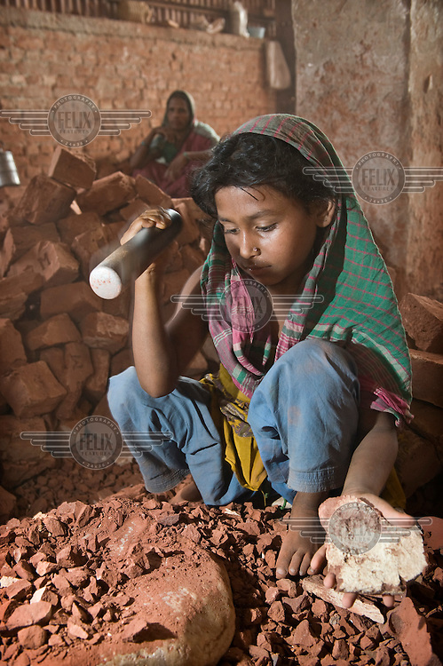 Eight year old Lima works breaking up brick and stone into ballast to be used in concrete. Many children are employed in this work, earning between 25-50 Euro cents a day.