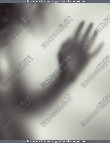 Young woman blurred hand behind frosted glass