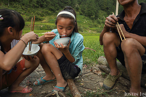 A family enjoys fresh grilled fish caught in their paddy field.