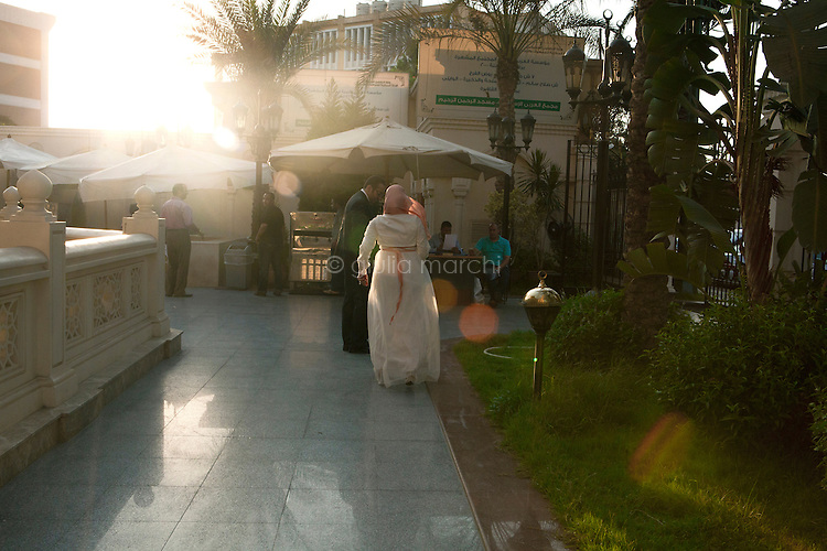 Egypt / Cairo / 14.7.2012 / Manar, a Sister, runs towards her new husband from El Rahman El Rahim Mosque where they have just been married. Abbasseya, Cairo, Egypt. July 14th, 2012.<br /> <br /> © Giulia Marchi