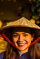 Beautiful Vietnamese woman wearing a Non la (conical palm leaf hat), Hoi An, Vietnam.