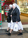 Pic shows: Oxford Street shopping on the last Saturday before Xmas 21.12.13<br /> two nuns in white habits have been shopping to the apple store  - one has a shopping bag possibly containing and iPhone<br /> <br /> <br /> <br /> <br /> Pic by Gavin Rodgers/Pixel 8000 Ltd
